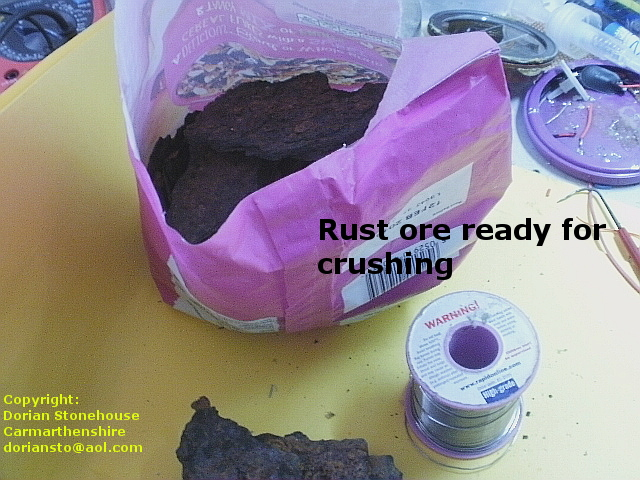 Bag of brown rust sits on the bench ready for crushing into powder.